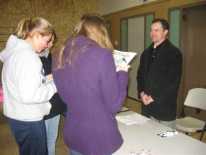A Great Northwest Federal Credit Union representative chats with youth during a financial workshop.