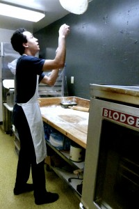 Cook Marco tosses pizza dough for waiting customers.