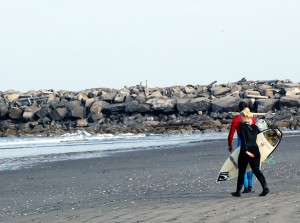 "Surfers walk down the beach at ""the jetty."""