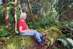 Janet Strong relaxes on the root of a hemlock tree on her property near McCleary, WA. Photo credit: Paul Dunn.