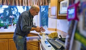Elma farmer Jay Gordon butters freshly made sourdough bread on a recent rainy morning in the kitchen of his home