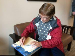 Susan Duvall signing check